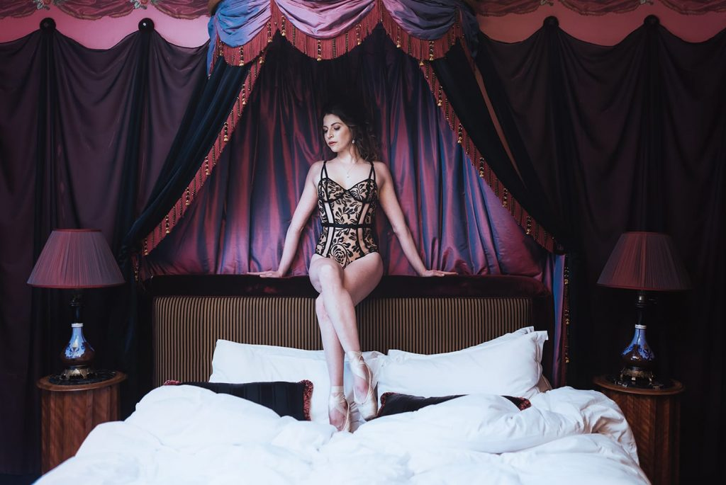 cute girl sitting on a bed's header during her pairs portrait and boudoir photoshoot with gloria villa photographer