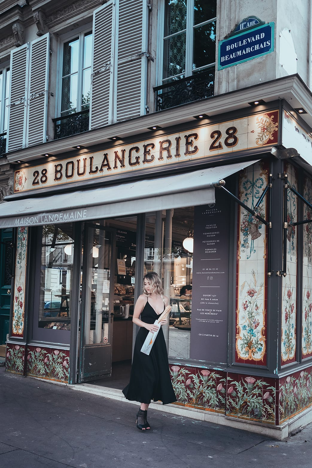 gorgeous girl walking out of a parisian boulangerie during her pairs portrait and boudoir photoshoot with gloria villa photographer