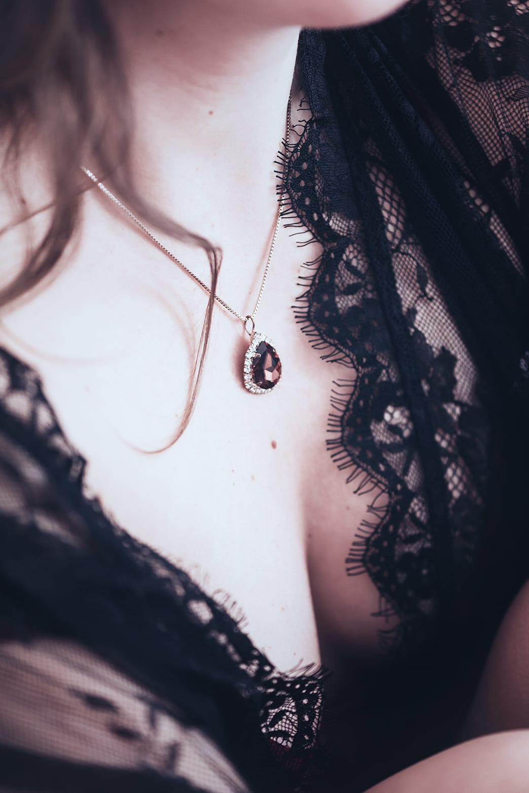 detail shoot of a girls breast with necklace during her pairs portrait and boudoir photoshoot with gloria villa photographer