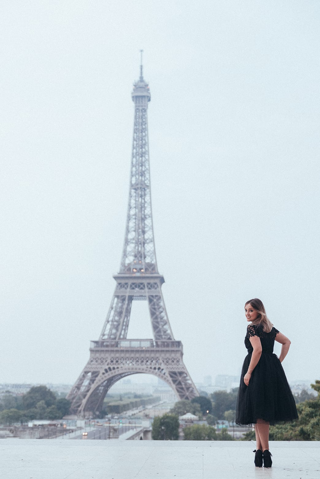cute girl standing in front of the Eiffel Tower