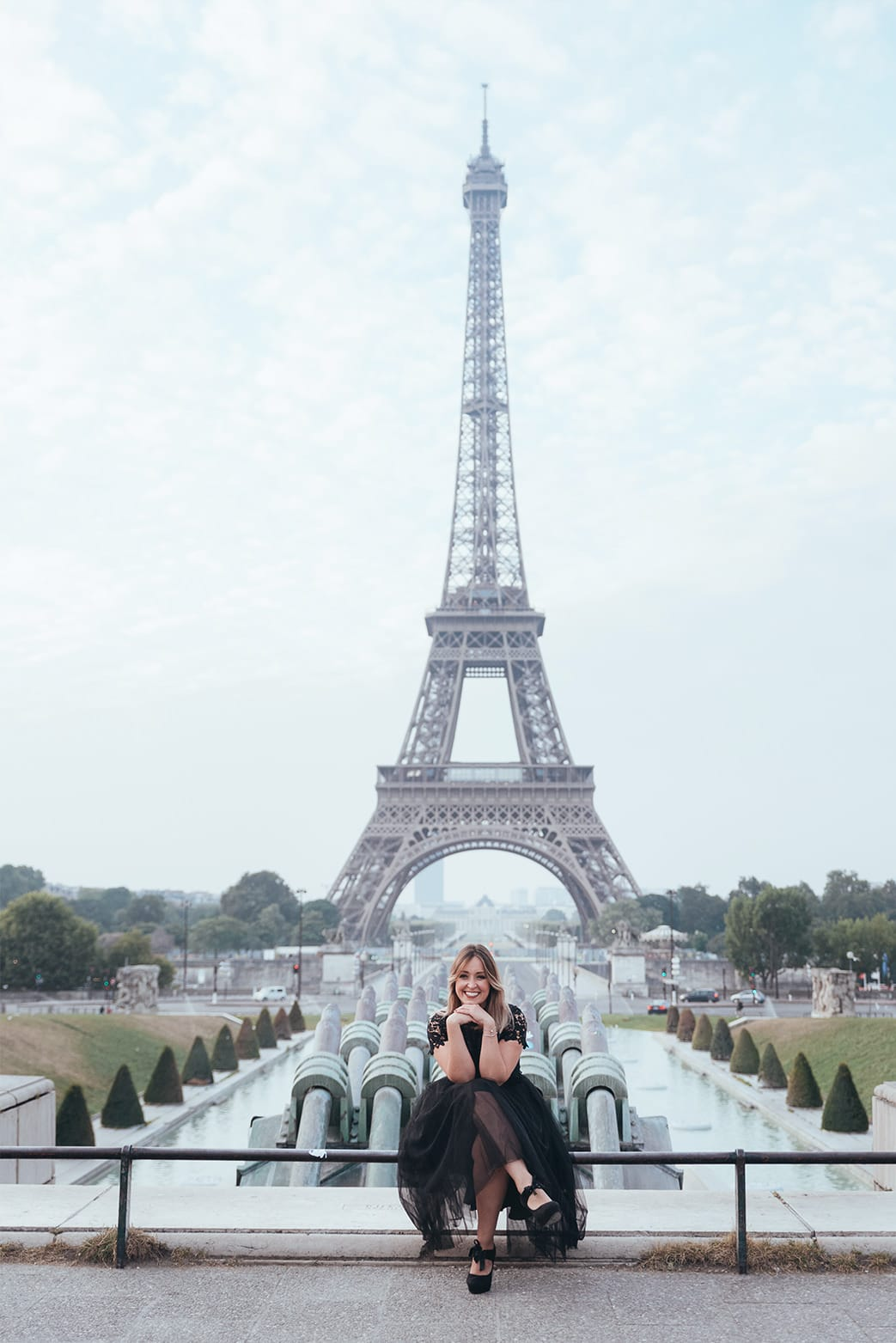 beautiful girl sitting in front of the eiffel tower during her boudoir photography session in Paris