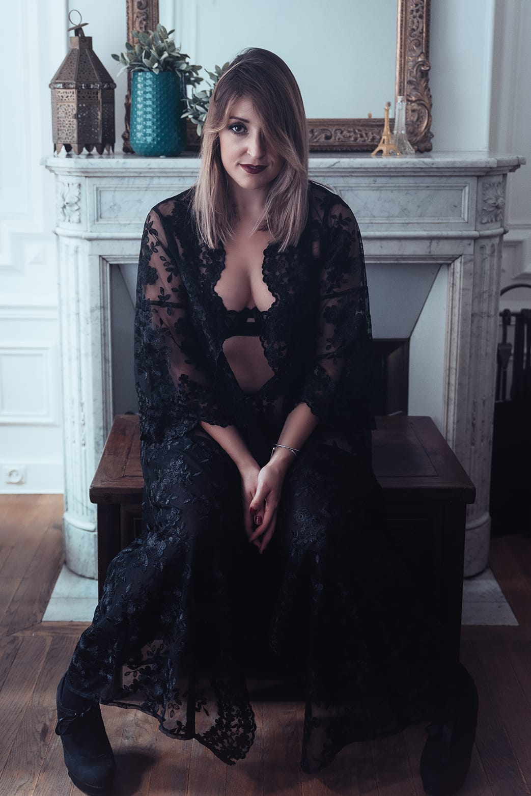 beautiful woman sitting in parisian apartment wearing a robe during her paris boudoir and portrait photoshoot with gloria villa photographer