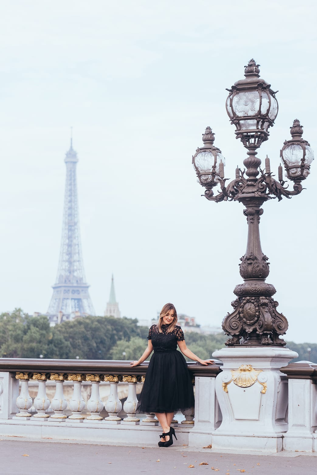 beautiful woman standing in parisian bridge with the Eiffel Tower in the background during her paris boudoir and portrait photoshoot with gloria villa photographer