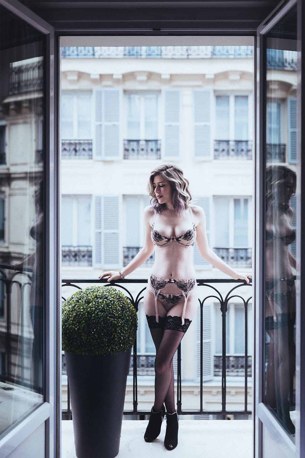 beautiful girl posing in lingerie on a parisian balcony during her portrait and boudoir photography session in Paris