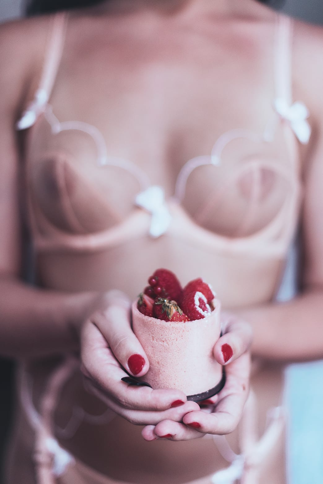 Woman holding a french dessert during her portrait and boudoir photoshoot in Paris by photographer gloria villa