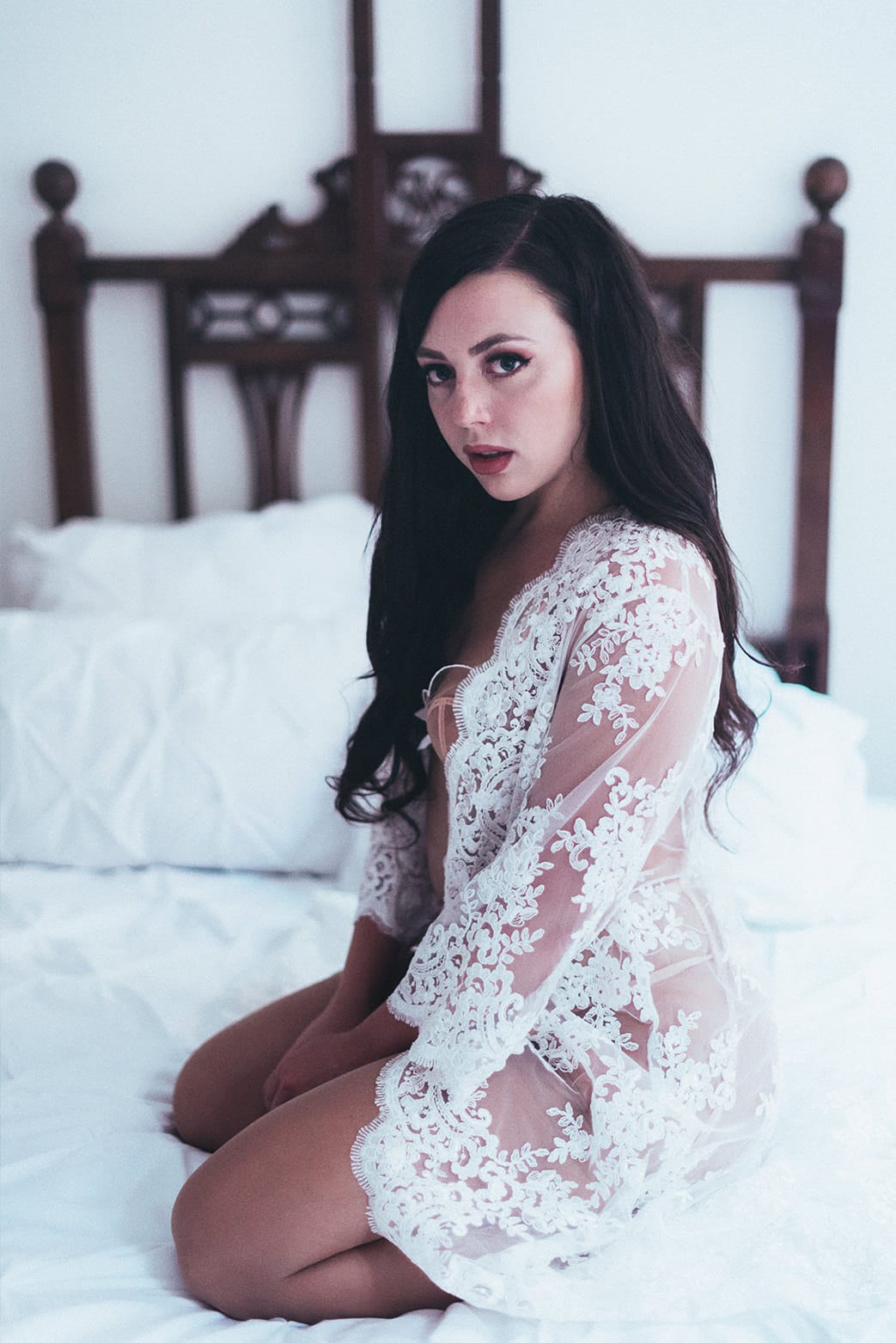 beautiful woman sitting on a bed wearing white lace robe during her pairs portrait and boudoir photoshoot with gloria villa photographer
