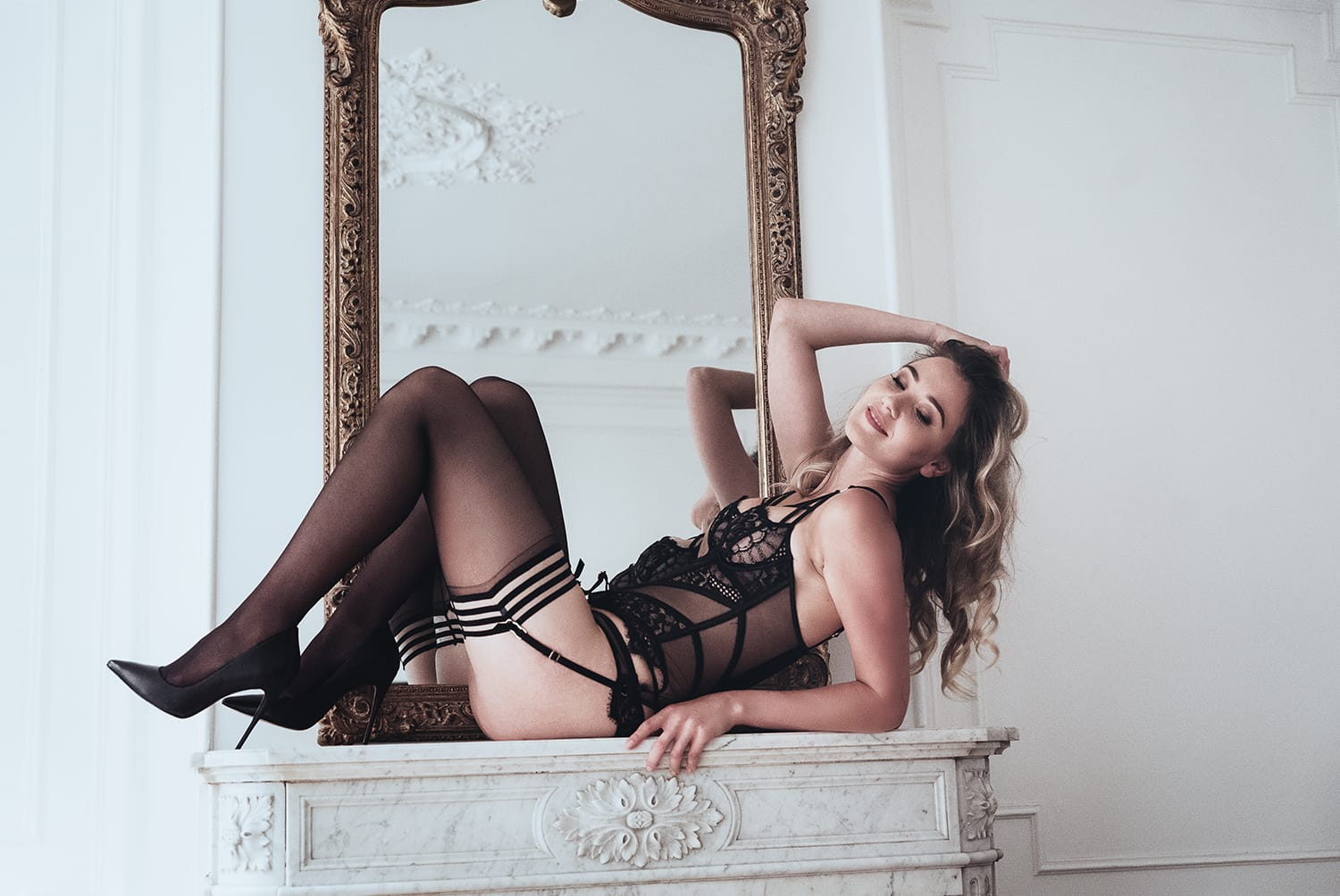 Beautiful girl on top of a parisian fireplace posing in lingerie during her portrait and boudoir photoshoot in Paris by Gloria Villa Photographer