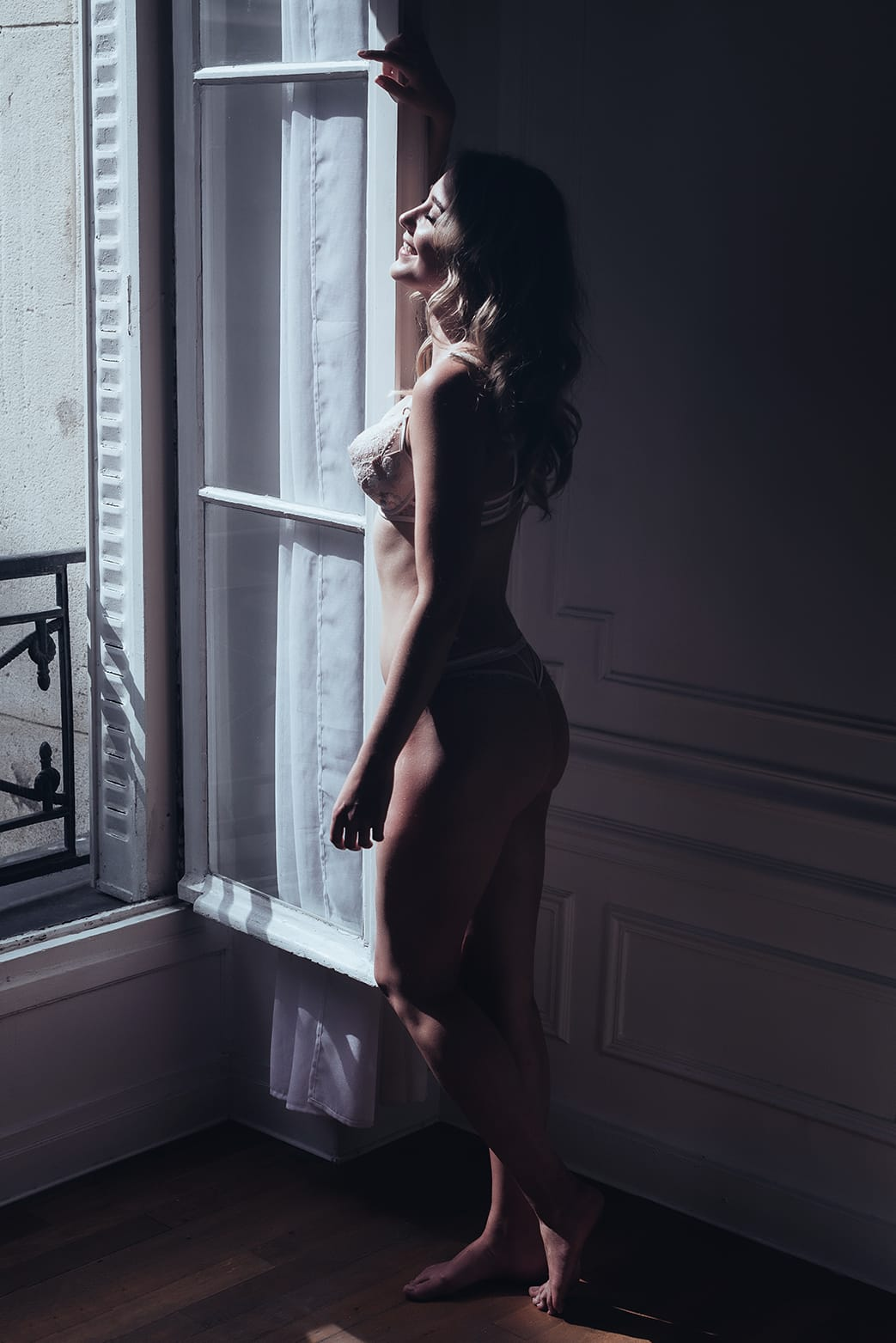 cute woman standing in front of a parisian window with lingerie during her pairs portrait and boudoir photoshoot with gloria villa photographer